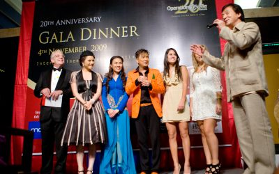 VNM_2009_Gala_Winick_11 From Left: Kenneth Atkinson, Board Chairman OPS Vietnam, Actress Ly Nah Ky, Singer My Tam, Singer Dam Vinh Hung, Jackie Chan, Students Danielle Winick of NY, and Grace Cosgrove of Ireland. Birthday cake in front. Operation Smile Vietnam 20th Anniversary Gala at the Intercontinental Hotel West Lake. Operation Smile's 20 year anniversary in Vietnam. (Operation Smile - Marc Ascher)